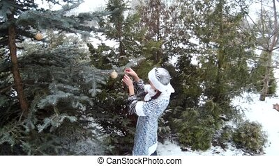Snow Maiden in forest hanging toys on a firm tree smiling...