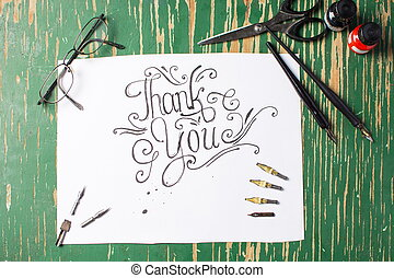 Thank you note calligraphy with writing equipment on the...
