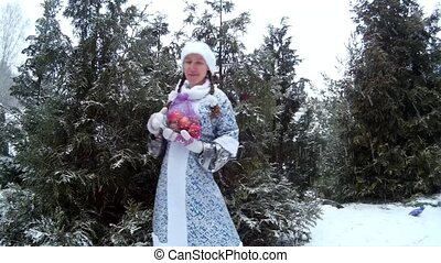 Snow Maiden in forest presents gift in front of pine tree Ukraine