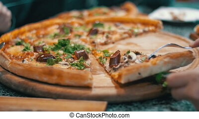 Pizza on a Wooden Platter in the Pizzeria - Pizza on a...