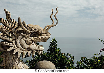Asian dragon made of white stones on a background the sea -...