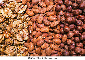 Peeled almonds, hazelnuts and walnuts kernel background or texture