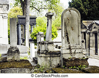 Tombstones in cemetery at dusk, gothic style crosses summer
