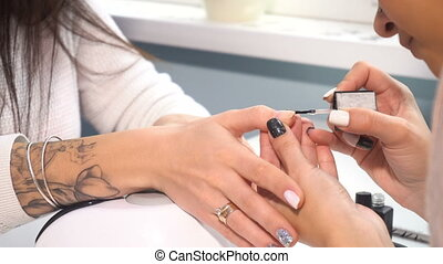 Manicure artist making professional manicure in spa salon...