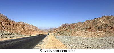 Empty road in rocky desert with blue sky