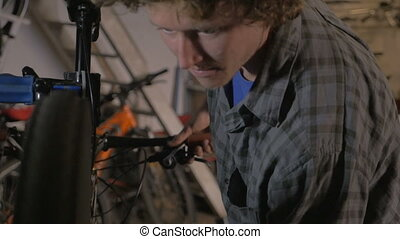 A millennial man bike mechanic adjusts the rear derailleur...