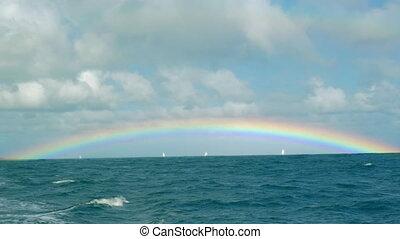 Rainbow over the blue ocean - Bright rainbow extending over...