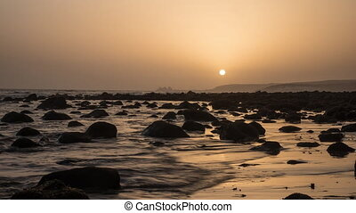 Timelapse of sea waves on coast with rocks at sunset -...