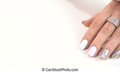 Hands of woman with beauty manicure at white table