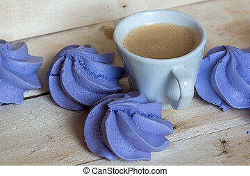 French blue meringue cookies and cup of coffee on white...