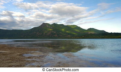 Waterside view of green forested hills - Green forested...
