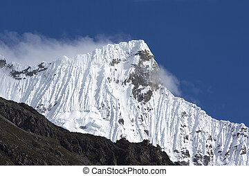 Snow covered mountain peak and blue sky, Cordillera Blanca,...