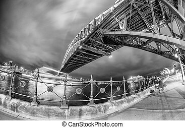 Black and white wide angle view of Sydney Harbour Bridge at night