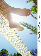 woman on hammock - cropped view of woman relaxing on hammock...