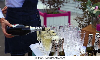 waiter pouring wine into glasses at a party close-up -...