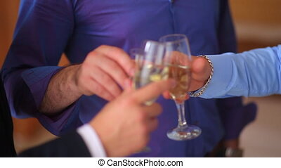 Men holding glasses of champagne making a toast near the...