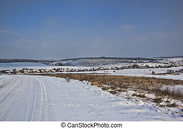Snow-covered road. Right plains and small hills covered with...