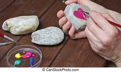 Painting on stone - Female hand is painting on a stone heart...