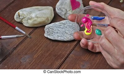 Smudge color before painting on stone - Woman's hand is is...