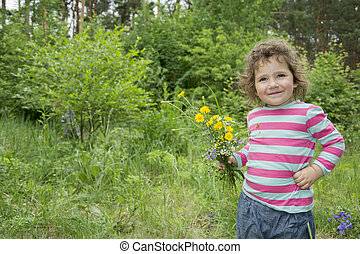 Spring in the forest a little funny girl holding a small bouquet of forest flowers.