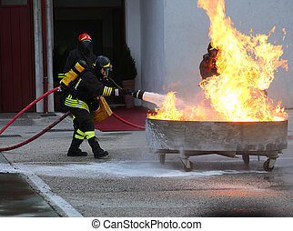 firefighters with oxygen tank extinguishing a fire with foam...