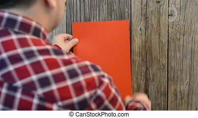 Man attaches red paper sheet on old wood wall board