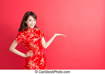 beauty woman wear cheongsam and show something to you in...