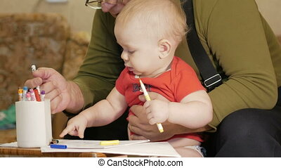 Attractive baby drawing with markers on paper with his...