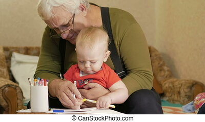 Attractive baby drawing with markers on paper with his grandfather. The child is allergic and reddened eyes.