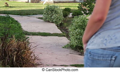 girl walking along a footpath - girl in jeans walking along...