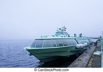 Passenger hydrofoil boat on the docks of Onego lake in foggy...
