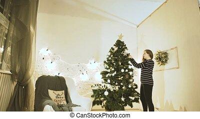 Christmas Day Celeb - Woman Hanging Christmas Ball on...
