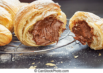 Croissant with chocolate filling on black wooden background