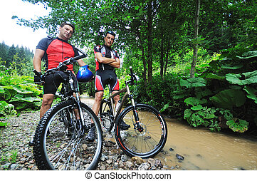 friendship and travel on mountain bike - two friends have...