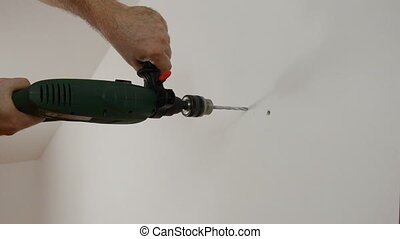 Drilling a Wall - Drilling a hole in a wall with an electric...