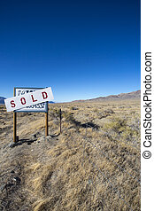 Sign board saying a farm land has been sold in the desert of...
