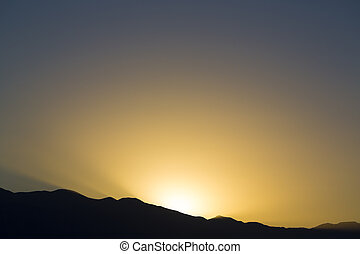 Dramatic sunset rays behind silhouette of mountain -...