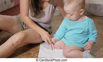 Attractive kid draws a pencil on the floor with mom at home. The boy is smiling and playing with his mother. The concept of family vacations