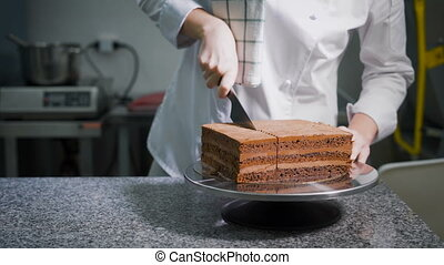 Kitchen. On a table ready chocolate cake. The worker of a...