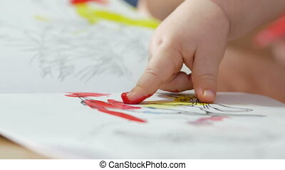 Hand the kid draws paints on a paper with his mother. The finger is dipped into the paint and leads for coloring. Close-up.