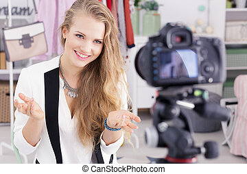 Beautiful woman filming tutorial, standing in front of...