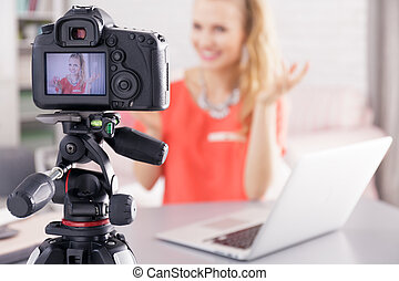 Woman filming her broadcast - Woman sitting beside desk with...