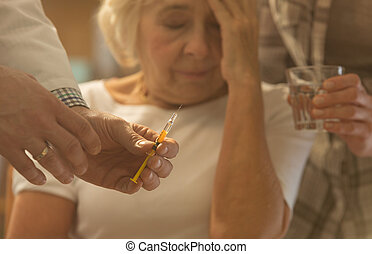 Senior woman, doctor holding syringe - Ill senior woman and...