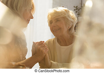 Woman supporting her old mother - Caring woman supporting...