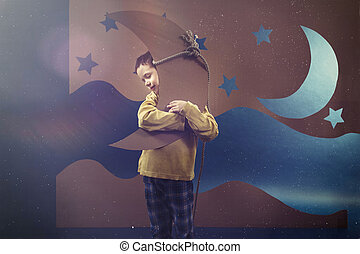 Boy hugging the moon - Boy wearing pyjamas and hugging the...