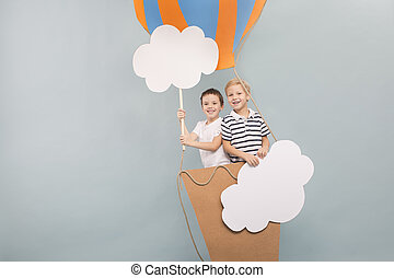 Friends flying in balloon among clouds