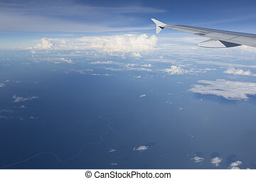 View of jet plane wing with clouds over the Amazonas State,...