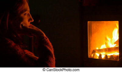 Girl near the Fireplace - Girl is looking meditative to the...