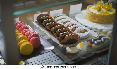 Cook pulls out a tray of cakes, lying in small bags called fudge niggets. In the showcase there is a set of desserts