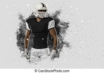 Football Player with a black uniform coming out of a blast...